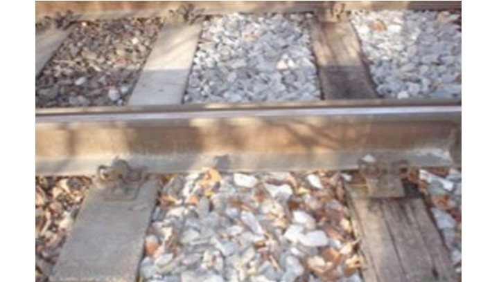 Composite rail sleepers in place next to worn wood rail sleeper